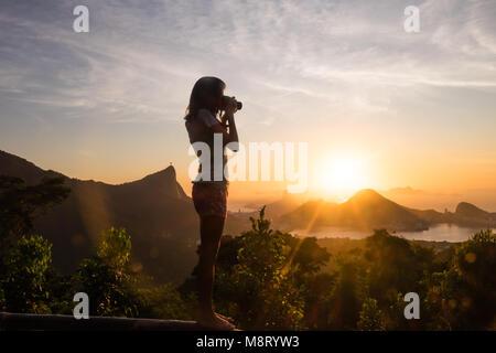 Girl Taking pictures of sunrise in Vista Chinesa, Rio de Janeiro, Brazil - Stock Photo