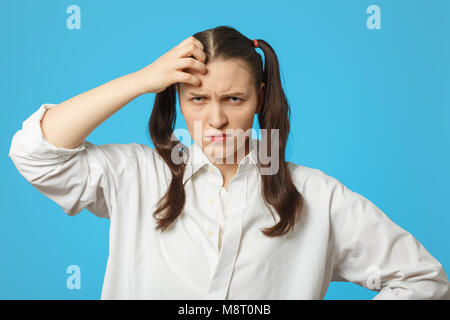 fun girl on blue background thinking looking at camera, scratches her head - Stock Photo