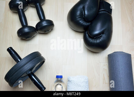 Kick boxing gloves, fixed-weight barbells, ab wheel, bottle of water, towel, rollable mattress on wooden background - Stock Photo