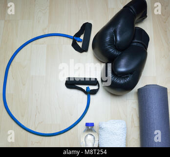 Rope in shape G , kick boxing gloves , bottle of water , towel and rollable mattress on wooden background - Stock Photo