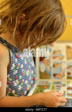 A young school age girl sits reading a book in a public library, CityLibraries Aitkenvale, Townsville Queensland, - Stock Photo