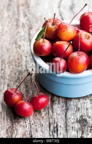 Fresh  wild apples in ceramic bowl on wooden table - Stock Photo