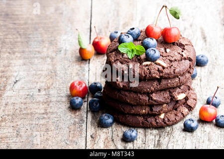 stack  of dark chocolate cookies with fresh blueberry and wild apples isolated on wooden table - Stock Photo
