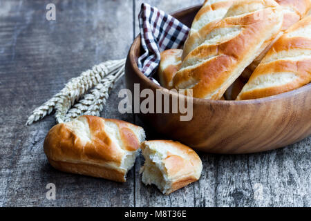 Mini  loaf bread in wooden bowl and wheat ears on wooden table - Stock Photo