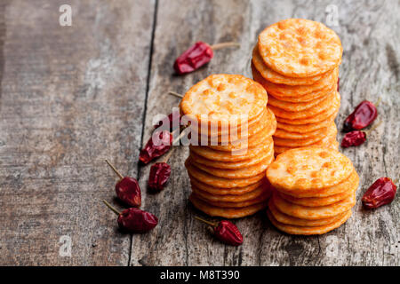 Round  shape rice cracker with chili pepper on wooden table - Stock Photo