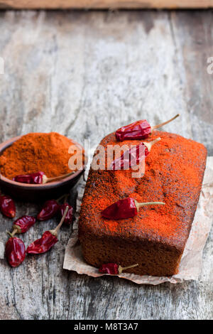 Delicious  chocolate cake with chili pepper on wooden table - Stock Photo