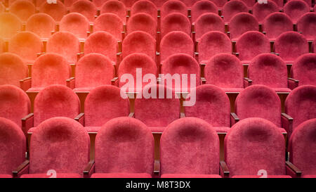 View from stairs on rows of comfortable red chairs in theater or cinema . Curve of Red Seats - Stock Photo