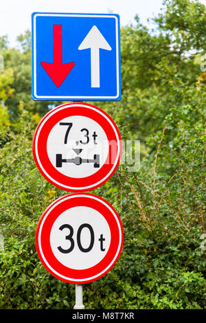 Three traffic signs near bridge in green nature - Stock Photo