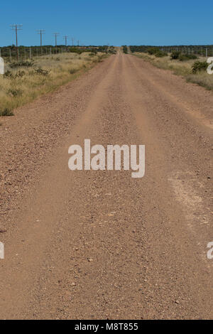 Long straight and dusty dirt road leading to a distant horizon image with copy space in portrait format - Stock Photo