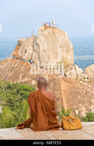 A Buddhist monk sits in contemplation on Mihintale and facing Aradhana Gala which pilgrims and tourists climb to - Stock Photo