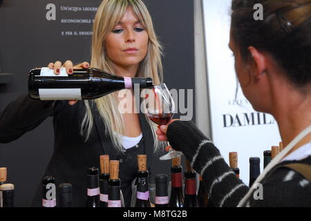 Blonde woman pouring red wine from the bottle to the glass of customer - Stock Photo