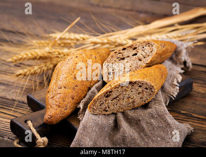 Buns of whole-grain flour with the addition of flax seeds on a wooden background. - Stock Photo