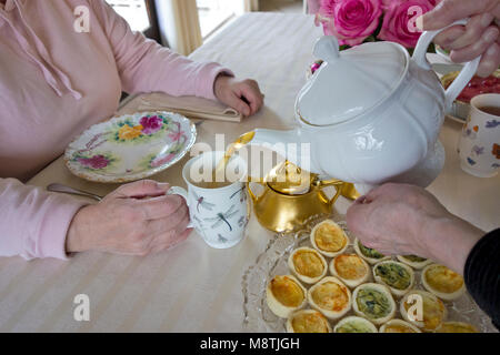 Two women friends having a cup of afternoon tea together.  Senior woman pouring a cup of tea for a friend during - Stock Photo