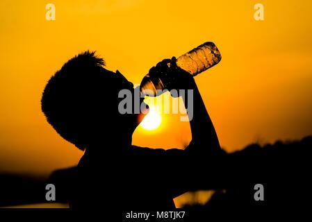 Silhouette boy drinking a bottle of water in sun set. - Stock Photo