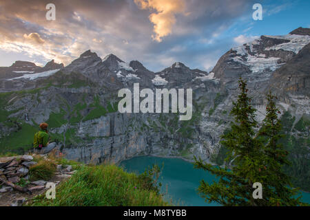 Lone hiker enjoying the beauty of this beautiful alpine lake at sunrise. Solitude in the mountains. Contemplation. - Stock Photo