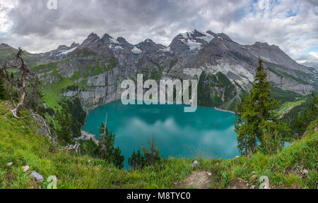 Great panoramic view from an overhang of Oeschinen lake, glacial lake in the Swiss Alps. Mountain cirque, range, - Stock Photo