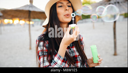 Happy young woman blowing bubbles on the beach - Stock Photo