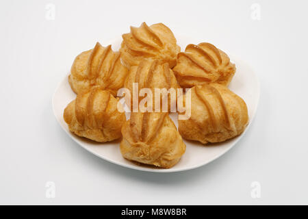 Cake eclair on a white plate. On a white background. - Stock Photo