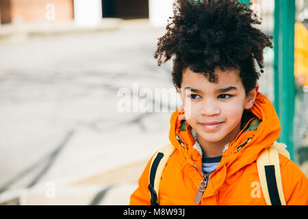 Portrait of a happy little school boy with orange coat and yellow backpack at the entrance of the school