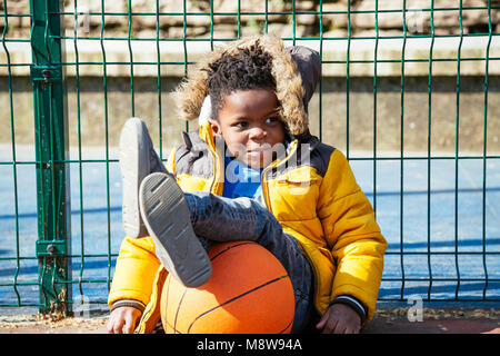 Funny little boy resting sitting on the ground with the legs on the basket ball - Stock Photo