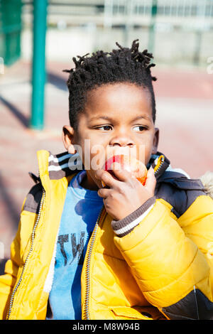 Cute little boy with a yellow coat eating a red apple at the school in a sunny day - Stock Photo