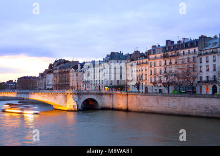 Boat on the Seine River passing by Pont de la Tournelle bridge in front of Ile Saint Louis, Paris, France - Stock Photo
