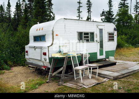 Old weathered caravan on a campsite. Monts-Valin, province of Quebec, Canada. - Stock Photo