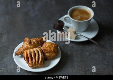 A continental-style breakfast with pastries such as croissants and chocolate rolls served with a hot cup of coffee. - Stock Photo