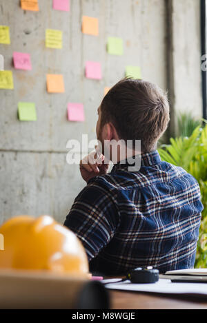Back of engineer sitting in office and look at colorful sticky message on cement wall. Work lifestyle concept. - Stock Photo