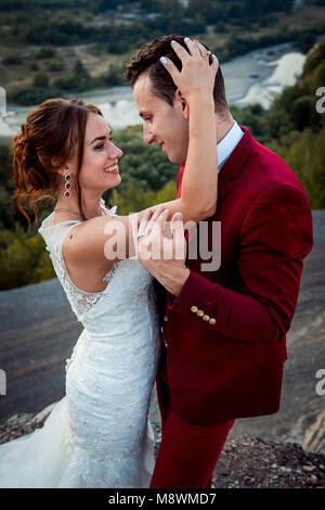 Half-length sensitive wedding portrait of the hugging couple. The charming smiling bride is stroking the hair of - Stock Photo