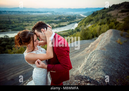 Tender portrait of the sensitive newlyweds at the background of the landscape of mountains, rivers and forests during - Stock Photo