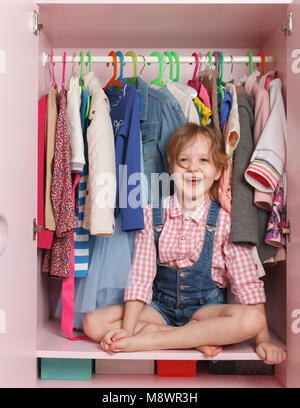 A little girl is sitting in a closet with a children's department. Storage system for children's things - Stock Photo