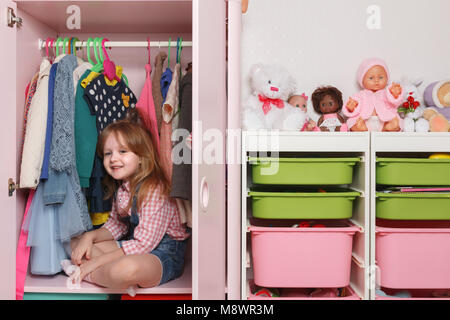 A little girl is sitting in a closet with a children's department. Storage system for children's things and toys - Stock Photo