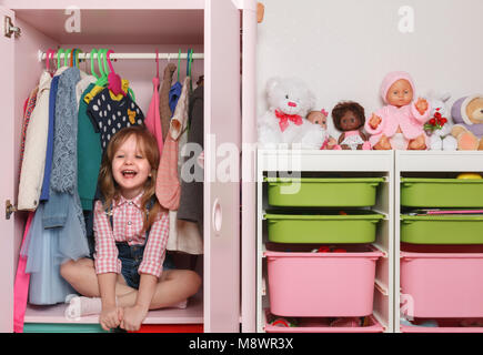 A little girl is sitting in a closet with a children's departmen - Stock Photo