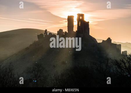 Corfe Castle, Dorset, UK.  21st March 2018.  UK Weather. Beams of sunlight shine through and around the silhouette - Stock Photo