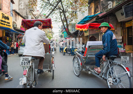 Vietnam rickshaw, two rickshaw drivers chat while taking their passengers on a tour of the Old Quarter in the center - Stock Photo