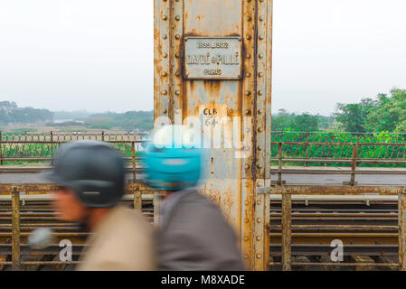 Long Bien bridge Hanoi, traffic streams past a pillar on the Long Bien Bridge bearing the nameplate of the French - Stock Photo