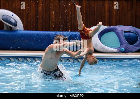 Two boys playing in the swimming pool on a summer day - Stock Photo