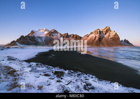 Scenic view of the Vesturhorn mountains during a warm sunset in Winter in Southeast Iceland. One alone photographer - Stock Photo