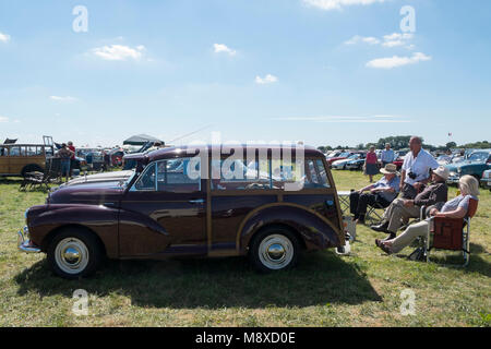 People sitting behind their burgundy 1950s Morris Traveller at the Gloucestershire Vintage Country Show in Cirencester - Stock Photo