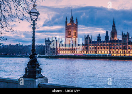 The Houses of Parliament along the river Thames in London at night. - Stock Photo