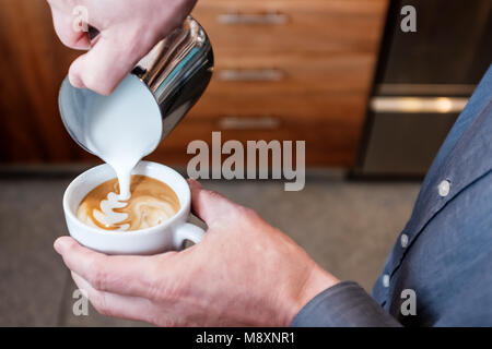 Professional barista pouring steamed milk from stainless steel tumbler into coffee cup making latte art on cappuccino - Stock Photo