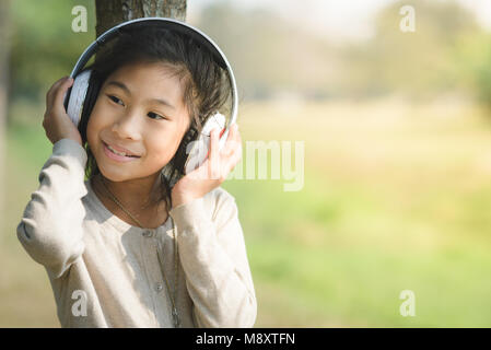 Happy girl using headphone and sitting under tree outside, lifestyle concept. - Stock Photo