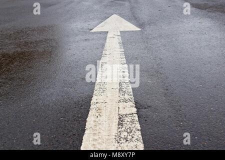 White painted forward arrow marking on dark wet road - Stock Photo
