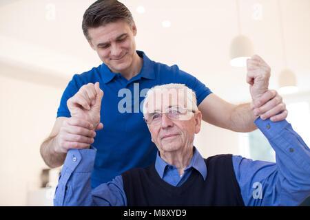 Male Nurse Assessing Senior Stroke Victim By Raising Arms - Stock Photo