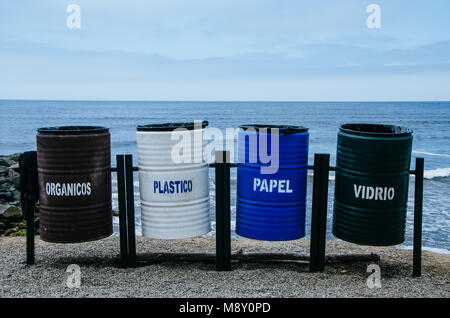 Recycling bins of different colors on the beach that says: organic = organic, plastic = plastic, paper = paper, - Stock Photo