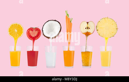 Fresh juice pours from fruits and vegetables in a glass on pastel pink background - Stock Photo
