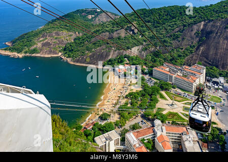 Arrival of the Sugar Loaf cable car to its first station after leaving its base on the Red beach in Urca district, - Stock Photo