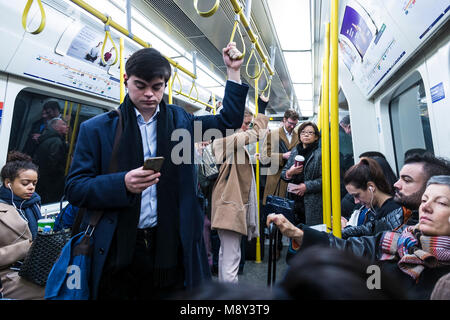 Commuters travelling to work on a London Underground tube train. - Stock Photo