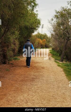 Man walking the dog on Path between vegetation in Santa Pola, Spain - Stock Photo